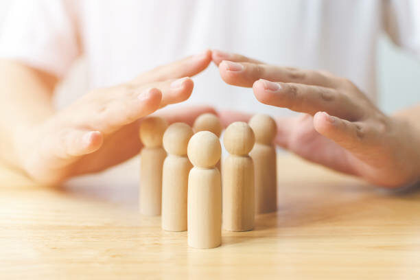 Two hands guarding 6 mini human figures symbolising protection