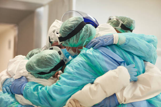 Clinicians dressed in PPE embracing